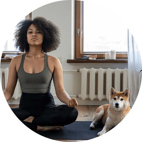 a woman meditating with her dog beside her